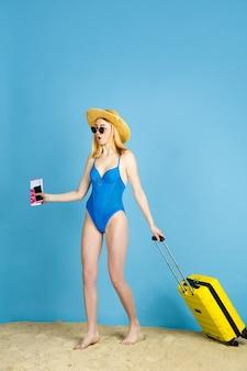 Kaartjes vasthouden. gelukkige jonge vrouw met zak die op reis op blauwe studioachtergrond wordt voorbereid. concept van menselijke emoties, gezichtsuitdrukking, zomervakantie, weekend. zomer, zee, oceaan, alcohol.