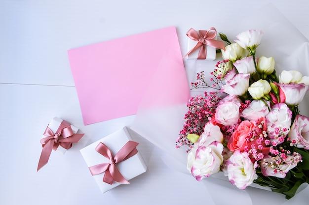 Kaartmodel met delicaat boeket en geschenkdozen. florale achtergrond. bovenaanzicht plat lag kerstkaart 8 maart, happy valentine's day, moederdag concept. kopieer ruimte voor tekst. vakantie wenskaart