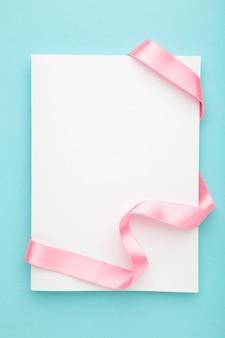 Kaartnota met roze lint op blauwe pastelkleuroppervlakte