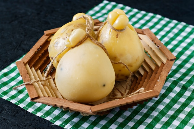 Kaas caciocavallo in een mand op een zwarte achtergrond. kaaspeer