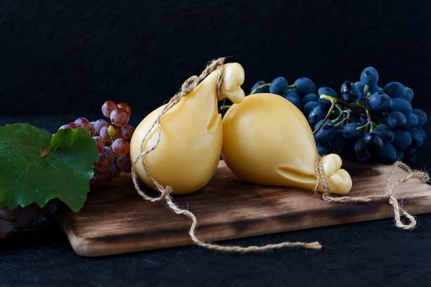 Kaas caciocavallo op een houten bord met druiven op een zwarte achtergrond. kaaspeer