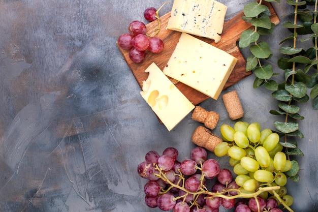 Kaas en druiven op een zwarte grijze concrete achtergrond
