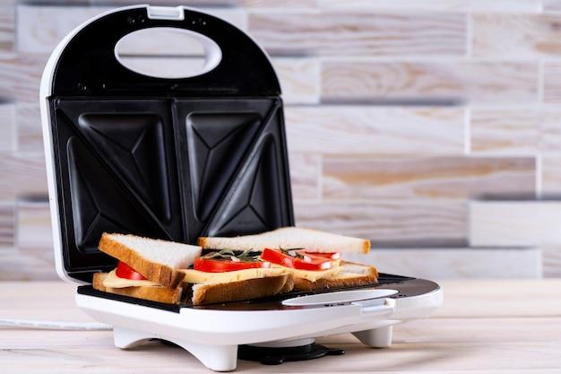 Kaas- en tomatensandwiches maken op een sandwichpers