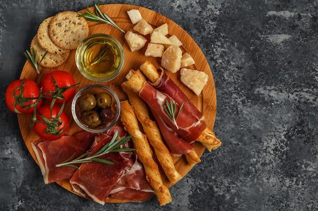Kaas en vlees voorgerecht selectie. prosciutto, parmezaanse kaas, stokjes brood, olijven, tomaten op een houten bord.
