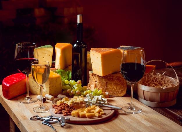 Kaas en wijn op een donkere tafel.