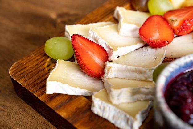 Kaas geassorteerd met fruit en jam op een houten bord. het serveren van de tafel en snacks tot de wijn voor het banket.
