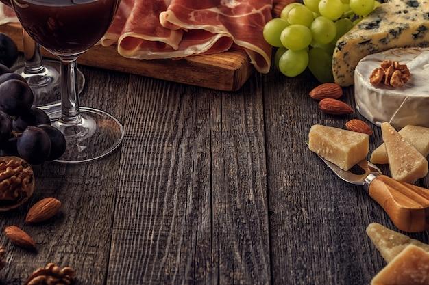 Kaas, ham, noten, druiven en rode wijn op houten achtergrond