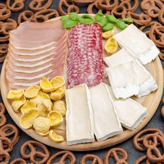 Kaas, ham, ontbijtgranen op een snijplank. krullende bruine koekjes