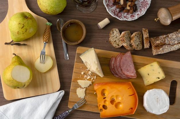 Kaas, ham, peren en brood op houten achtergrond