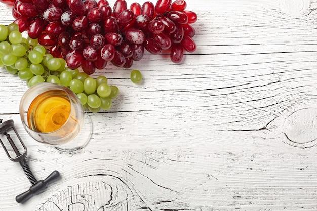 Kaas, honing, druif, noten en wijnglas op wit houten bord. bovenaanzicht met kopie ruimte.