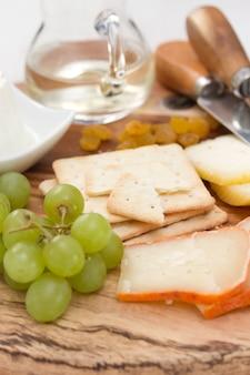 Kaas met koekjes, druiven en witte wijn
