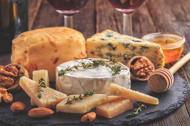 Kaas, noten, honing en rode wijn op houten achtergrond