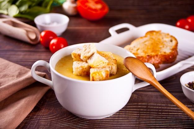 Kaas- of uiensoep met toastbrood in een witte kom