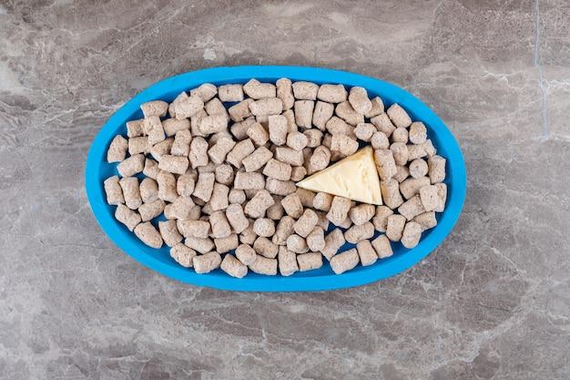 Kaas op de broodkruimels in de kom naast de spies, op het marmeren oppervlak