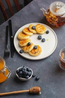 Kaas pannenkoeken met bosbessen, honing, bloemen thee geschroeid op blauwe steen achtergrond.