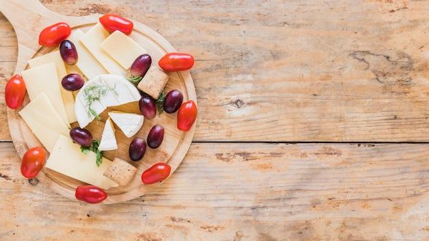 Kaas plakjes en blokken geserveerd met druiven en kerstomaatjes op snijplank over het bureau