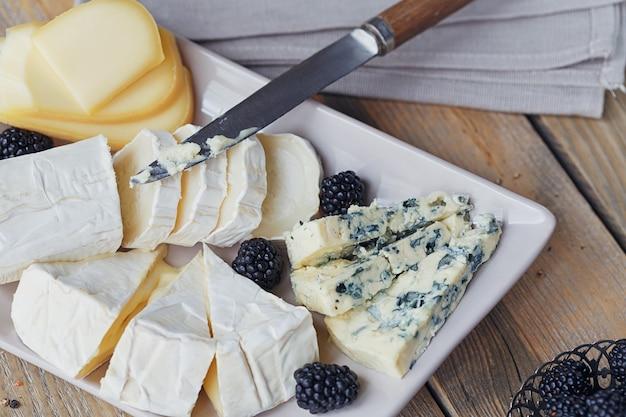 Kaas plankje. assortiment van kaas met bessen op houten achtergrond.
