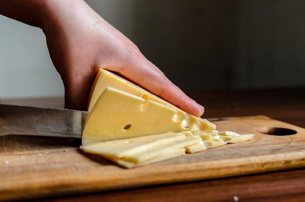 Kaas snijden op een houten bord.