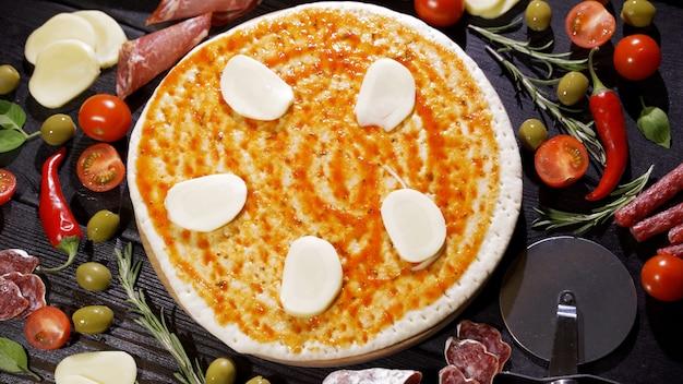 Kaas toevoegen aan de pizza