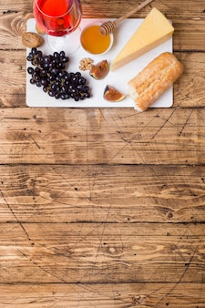 Kaas, wijn, baguette druiven vijgen honing en snacks op de rustieke houten tafelblad met kopie ruimte.