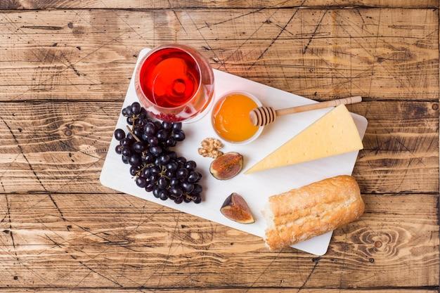 Kaas, wijn, baguette druiven vijgen honing en snacks op het rustieke houten tafelblad.