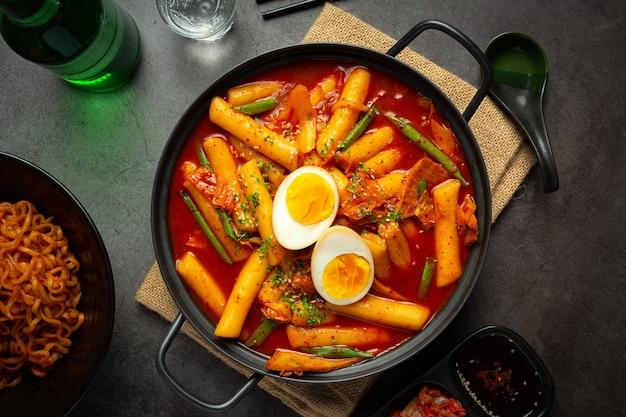 Kaasachtig koreaans traditioneel voedsel tokbokki op zwarte raadsachtergrond. lunch gerecht.