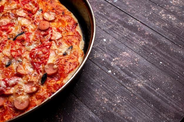 Kaasachtige tomatenpizza met olijven en worstjes in pan op bruin bureau, de kaasworst van het pizzamaaltijd snel voedsel