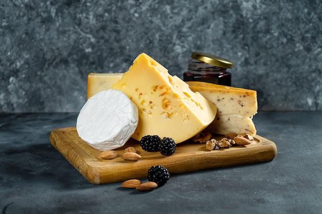 Kaasassortiment op een donkere steenachtergrond met exemplaarruimte. verschillende soorten: camembert, kaas met kruiden, hollandse kaas op houten snijplank. amandel, bramen en jam met kaas. zachte focus