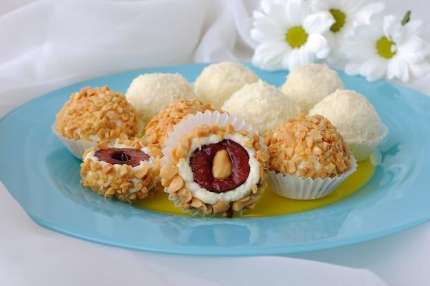 Kaasballetjes gevuld met kersen in pinda's en kokosvlokken