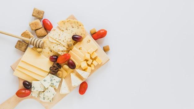 Kaasblokjes en plakjes met vrolijke tomaten, walnoten, druiven en koekjes op witte achtergrond