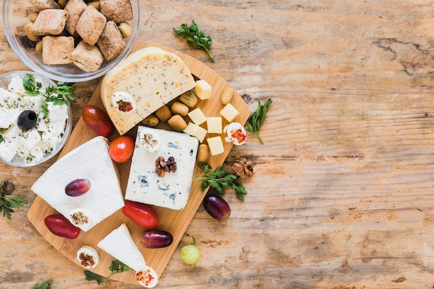 Kaasblokken met tomaten, peterselie en druiven op houten lijst