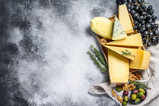 Kaasbord geserveerd met druiven, crackers, olijven en noten. diverse heerlijke snacks. bovenaanzicht copyspace-achtergrond