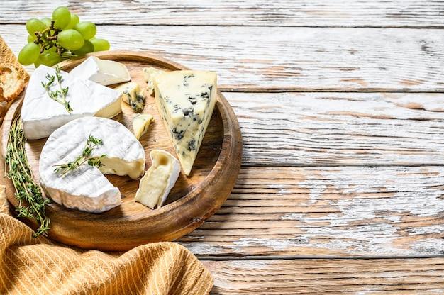 Kaasbord met camembert, brie en blauwe kaas met druiven. witte houten achtergrond. bovenaanzicht. kopieer ruimte