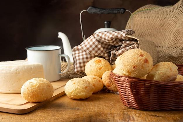 Kaasbrood, braziliaans ontbijtarrangement, kaasbrood, witte kaas, waterkoker en toebehoren, donkere abstracte achtergrond, selectieve aandacht.