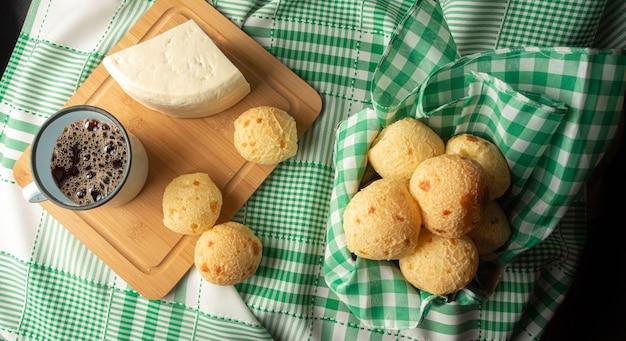 Kaasbrood, braziliaans ontbijtarrangement, pao de queijo, witte kaas, waterkoker en accessoires, groene handdoek, donkere abstracte achtergrond, bovenaanzicht.