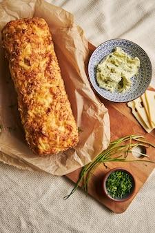 Kaasbrood met kruidenboter op een houten plaat met kruiden