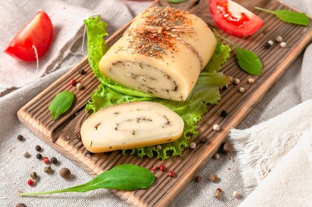 Kaasbroodje met olijfkruiden op een slablad. er wordt een stuk afgesneden. kaas op een houten bord. detailopname. gedecoreerd met rucola, kruiden en tomaten. achtergrond grijze linnen stof. detailopname.