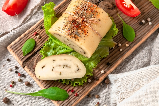 Kaasbroodje met olijfkruiden op een slablad. er wordt een stuk afgesneden. kaas op een houten bord. gedecoreerd met rucola, kruiden en tomaten. achtergrond grijze linnen stof. uitzicht van boven.