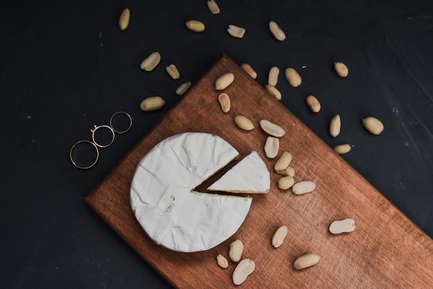 Kaascamembert met schimmel en noten en trouwringen op de houten snijplank