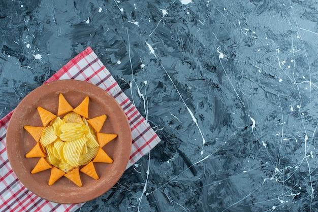 Kaaschips en kegelchips in een bord op theedoek, op de marmeren tafel.