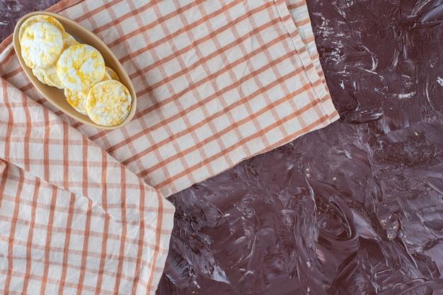 Kaaschips in een bord op een theedoek, op de marmeren tafel.
