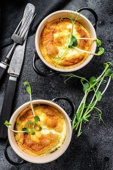 Kaasomelet, omelet met microgreens in een pan. zwarte achtergrond. bovenaanzicht.