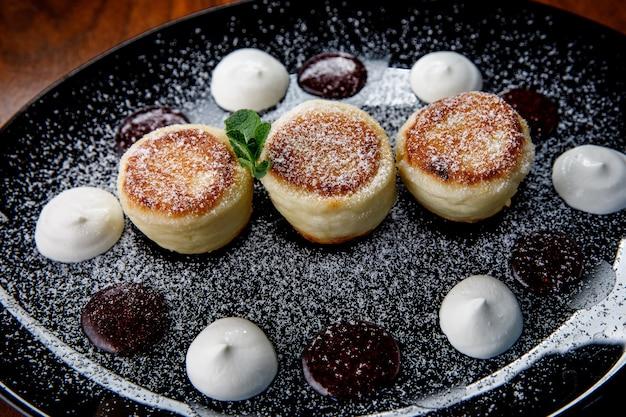 Kaaspannenkoek, cheesecakes met zure room, jam en munt op een bord. ontbijt.