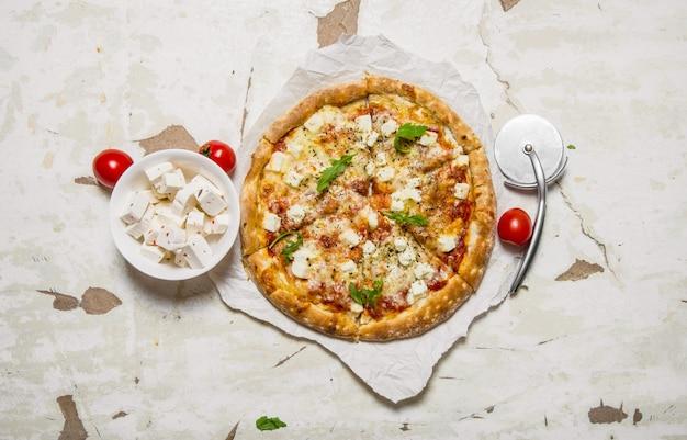 Kaaspizza met kruiden en verse kaas. op rustieke achtergrond. bovenaanzicht