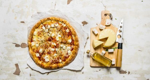 Kaaspizza met tomaten, olijven en verse kaas op rustieke achtergrond