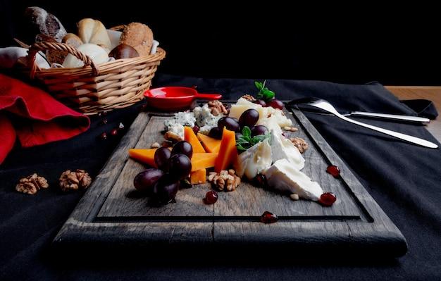 Kaasplaat geserveerd met druiven, honing en noten op een houten achtergrond. diverse soorten kaas