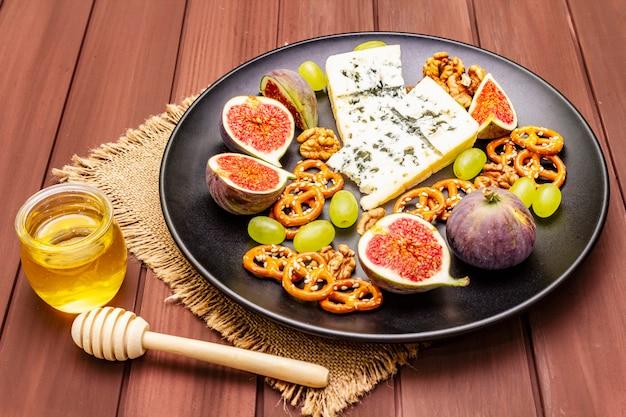 Kaasplaat met blauwe kaas, honing, walnoten, vijgen, druiven, pretzels