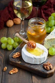 Kaasplaat met druiven, honing en noten op donkere achtergrond.