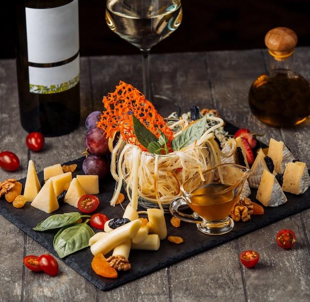 Kaasplaat met glazen beker gerookte kaas in het midden
