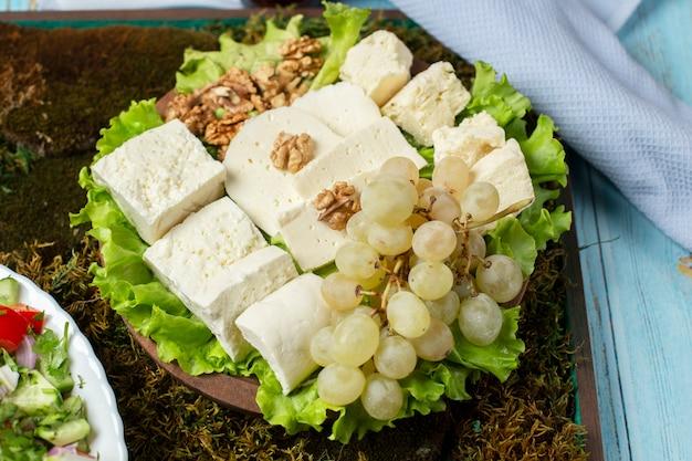 Kaasplaat met witte kaas, groene druiven en noten.